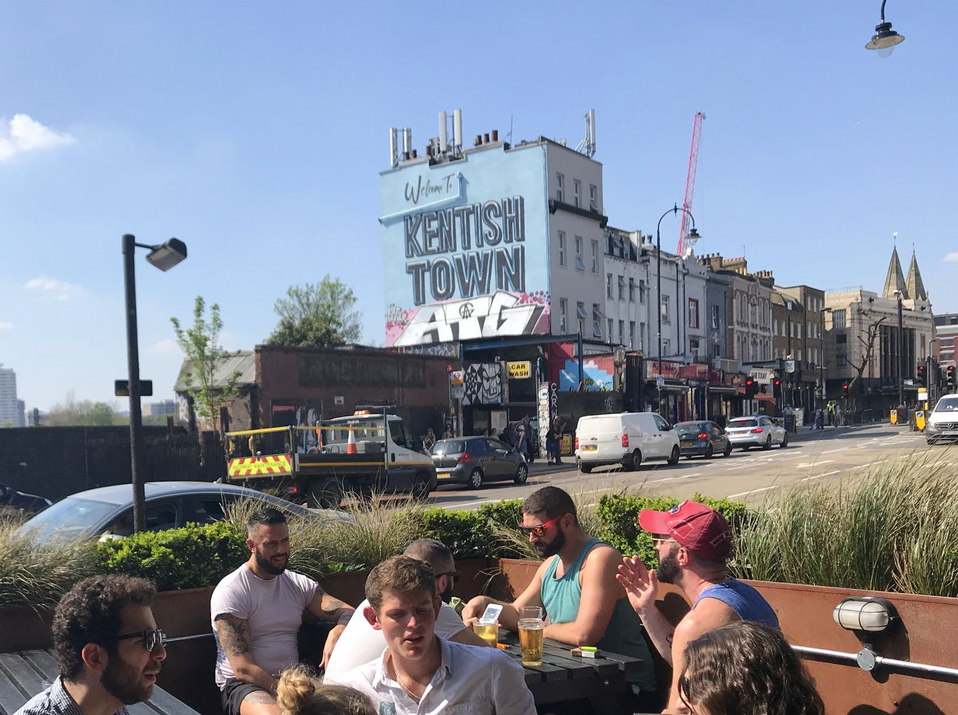 People sitting at pub table with Kentish Town mural in the background