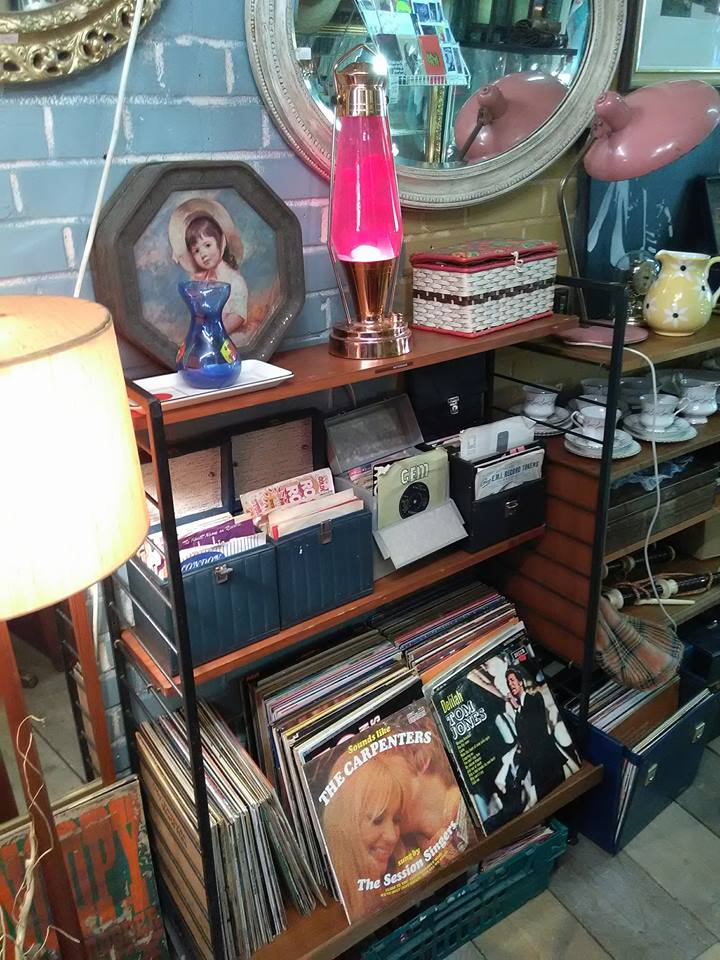 A mirror, a lava lamp and old records on a shelf in Aladdin's Cave