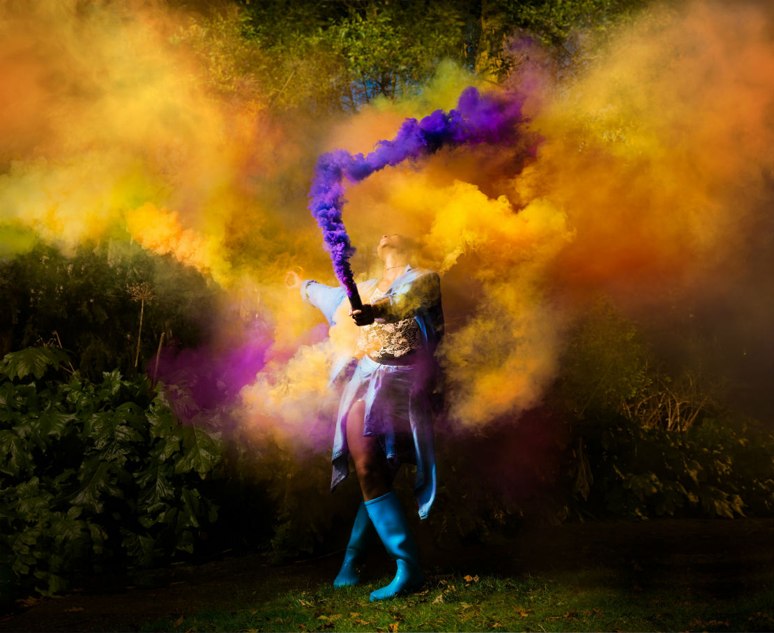 Shakespeare performer concealed by colourful smoke