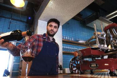 Authentique owner Alex pours a glass of red wine at the bar