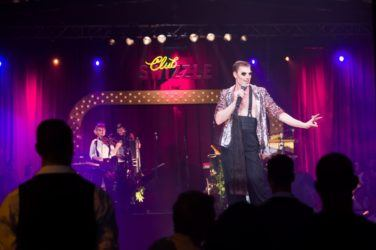 A performer leads the show at Club Swizzle